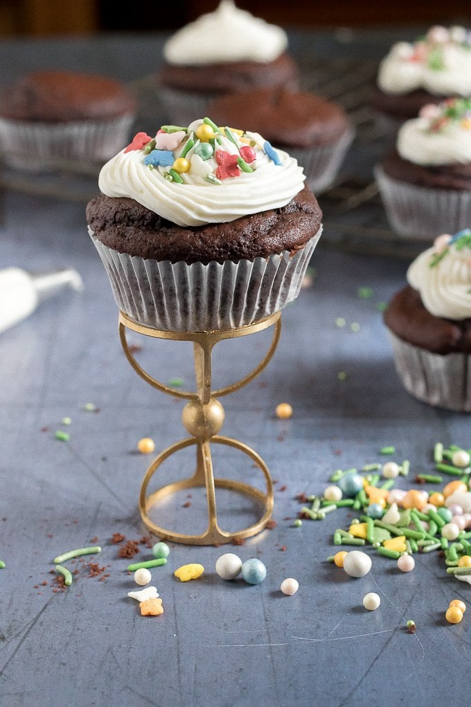 A chocolate vegan cupcake on a golden cupcake stand with vanilla icing and sprinkles. Get the easy vegan chocolate cupcakes recipe now!