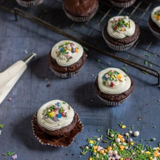 Easy vegan chocolate cupcakes with white icing and colourful sprinkles on a cooling rack