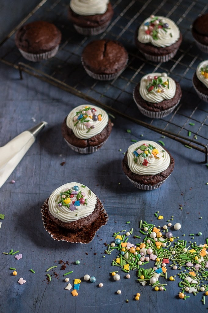 cupcakes with white icing and colourful sprinkles on a cooling rack