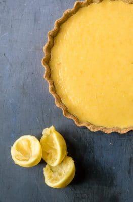 Overhead shot of lemon tart with chamomile crust next to lemons