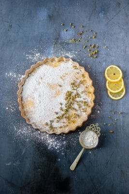 Lemon Tart with Chamomile Crust and Chamomile infused powdered sugar on a dark blue background with slices of lemon