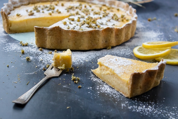 A fork full and slice of lemon tart with chamomile crust and chamomile infused icing sugar.