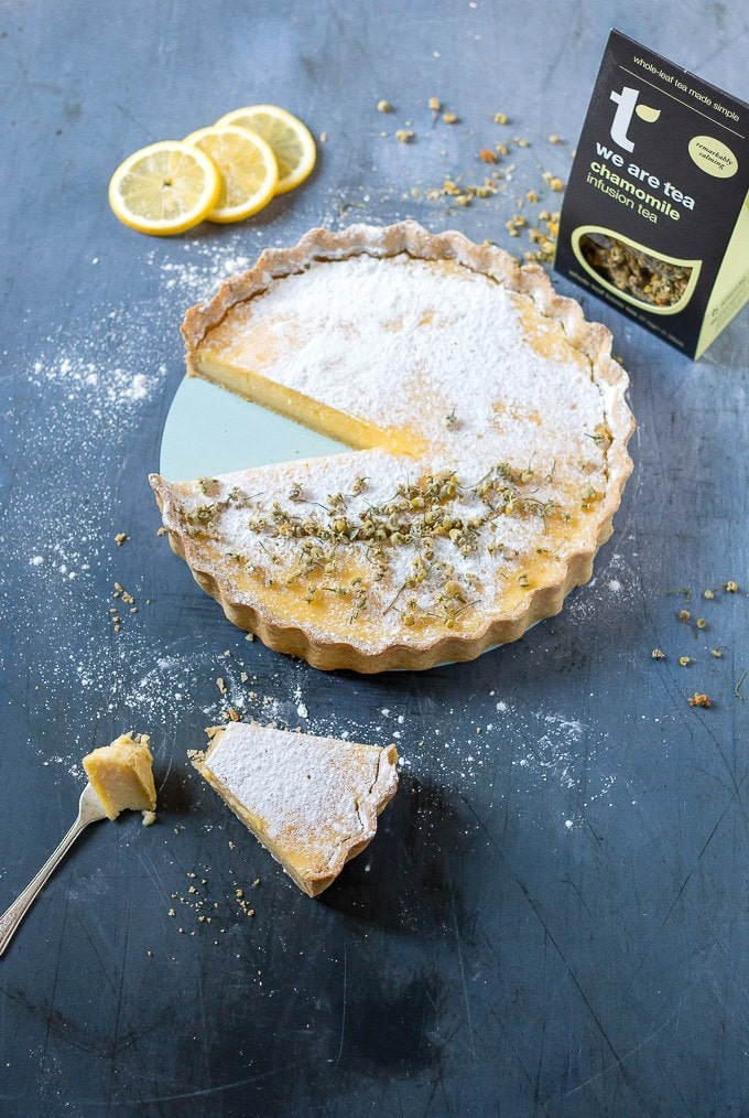 A slice from a lemon tart with chamomile crust next to a box of We Are Tea chamomile tea