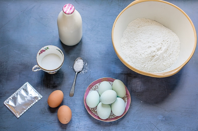 How to make easy Italian braided Easter bread - flat lay of ingredients: flour, milk, eggs, sugar, salt, yeast.