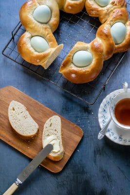 Two slices of fluffy Easter bread spread with butter, next to a cup of tea.