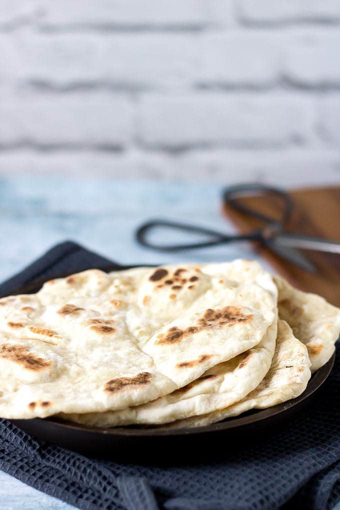 Stack of naan flatbreads on a wooden plate on a tea towel.