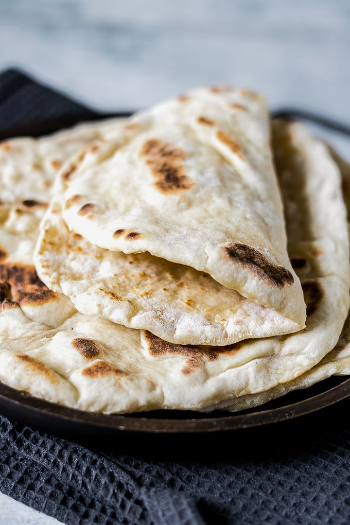 A folded fluffy yeast-free naan bread on a plate of other naan breads.
