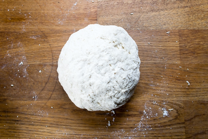 Ball of dough on wooden counter.
