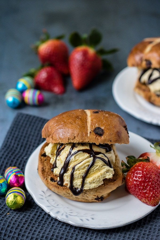 Three ingredient hot cross bun ice cream sandwiches served on a plate with a drizzle of chocolate sauce and a few strawberries.