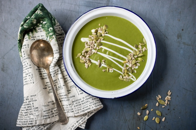 A bowl of bright green quick and easy kale soup with a drizzle of cream and a sprinkle of seeds. Easily vegan. Gluten-free.