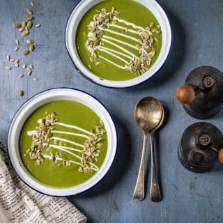 Two bowls of kale soup served with seeds and a drizzle of cream, on a table with vintage spoons and salt and pepper shakers.