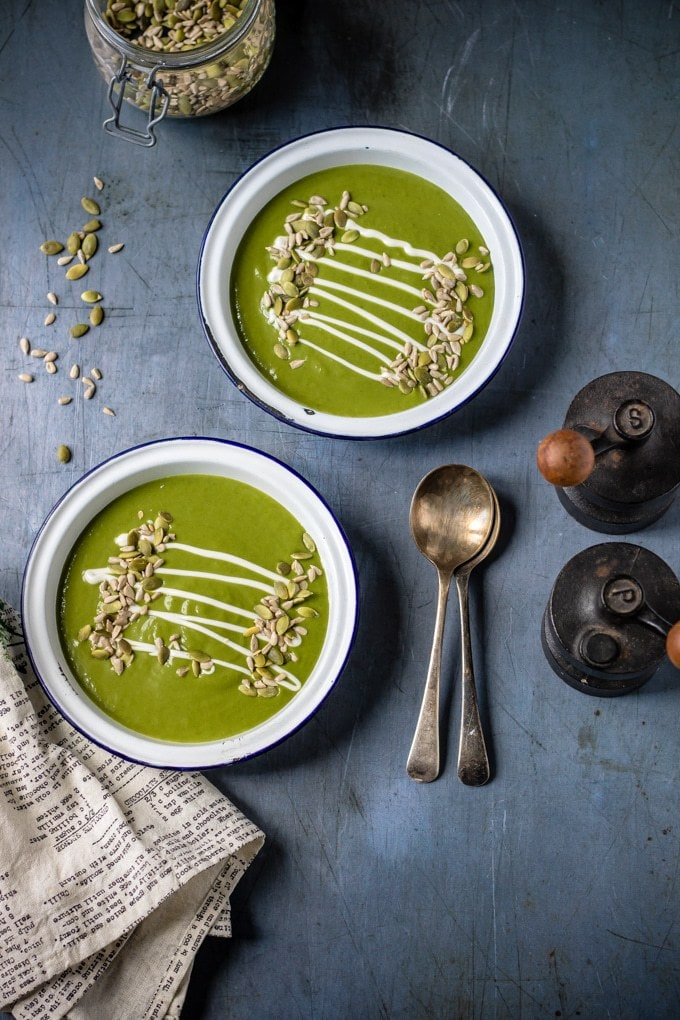 Two bowls of kale soup served with seeds and a drizzle of cream.