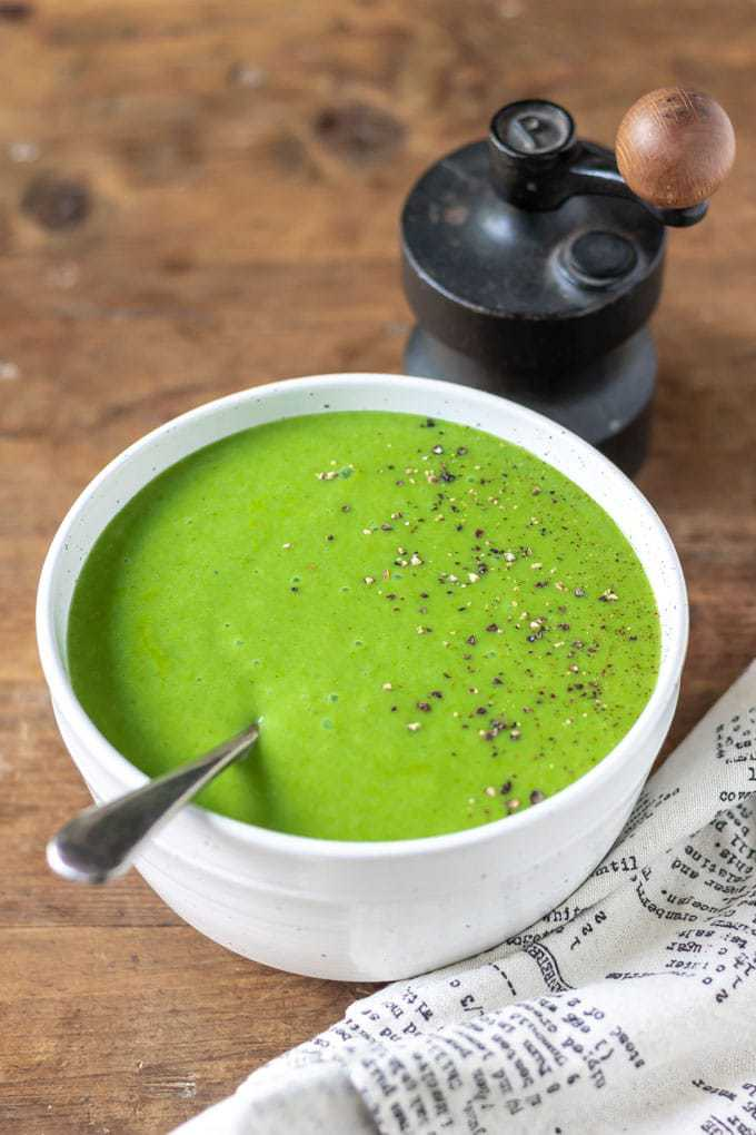 Easy kale soup recipe. A bowl of bright green blended kale soup with fresh pepper grinded on top.