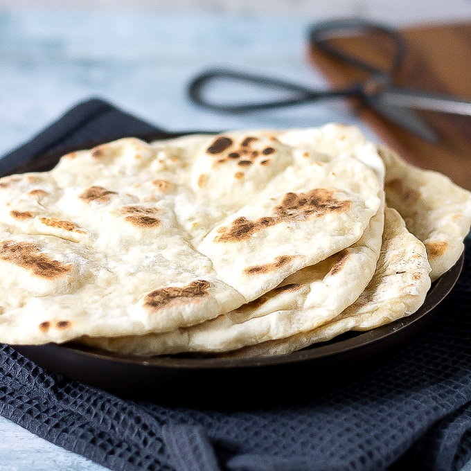 Stack of naan breads on a plate.
