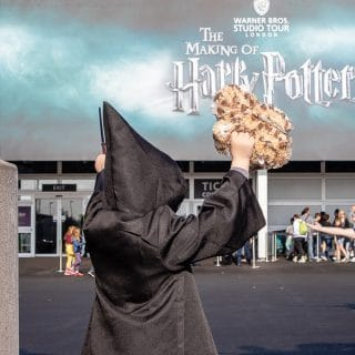 Child dressed as a wizard in front of the Harry Potter Tour sign at Warner Bros Studios, London