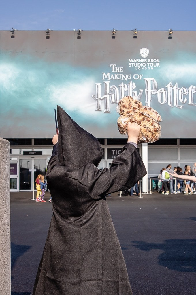 Child dressed as a wizard in front of the Harry Potter studio tour sign at Warner Bros Studios, London