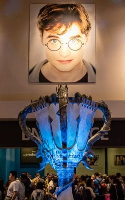 The lobby at the Harry Potter Studio Tour, London with a giant Goblet of Fire and large picture of Daniel Radcliffe as Harry Potter.