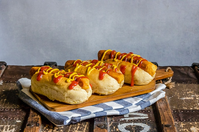 A wooden board with three lentil carrot hot dogs in buns with mustard and ketchup