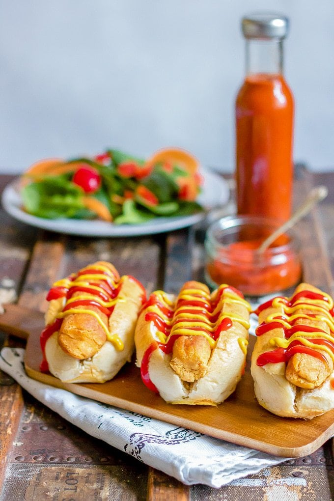 Lentil carrot veggie dogs in buns with ketchup and mustard in front of a bottle of ketchup and a salad