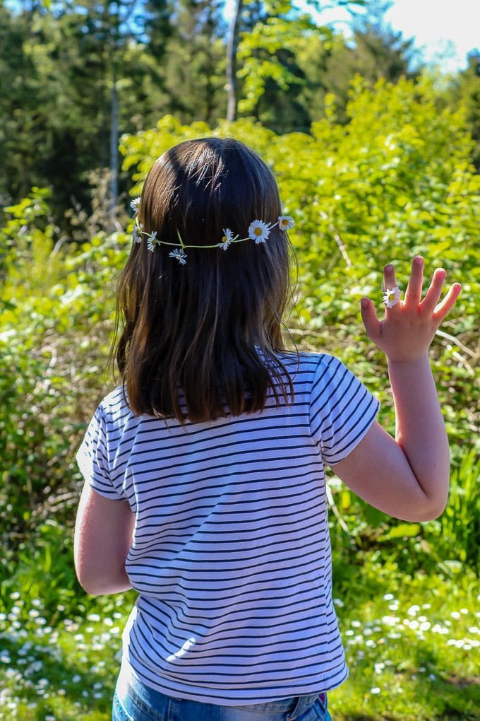 Girl with a daisy chain headband waving