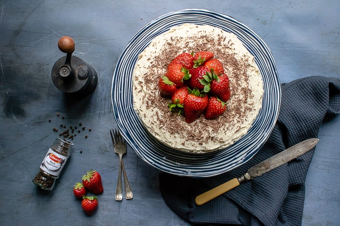 Overhead shot of easy one-bowl chocolate cake with vanilla black pepper buttercream, topped with shaved dark chocolate and fresh strawberries
