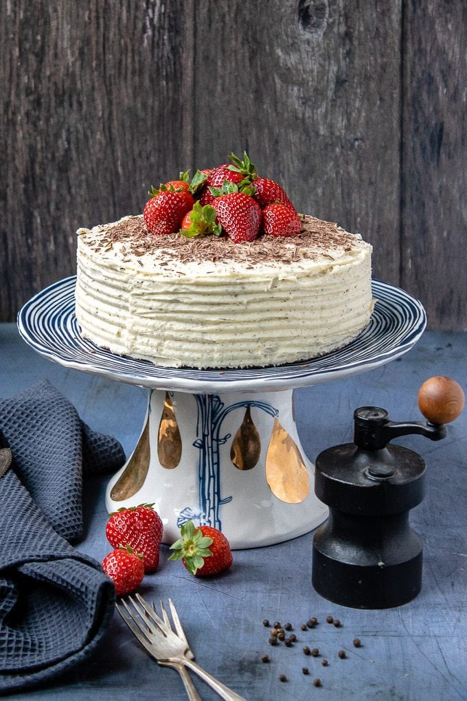 An easy one-bowl chocolate cake on a cake stand topped with shaved dark chocolate and fresh strawberries with a vanilla black pepper buttercream frosting.