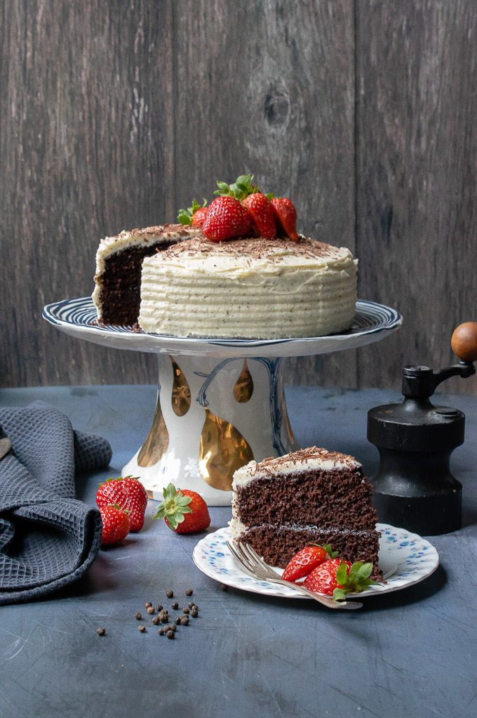 An easy one-bowl chocolate cake on a cake stand topped with shaved dark chocolate and fresh strawberries with a vanilla black pepper buttercream frosting, with a slice on a plate next to it.