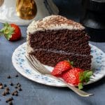 Close up of a slice of fluffy and moist one-bowl chocolate cake with a vanilla black pepper buttercream and fresh strawberries