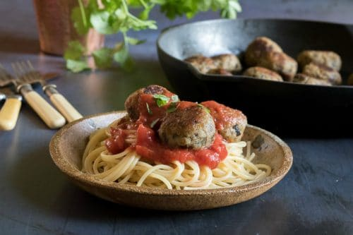 A plate of spaghetti with tomato sauce and (aubergine) eggplant meatballs and vegan parmesan cheese sprinkled on top, with a cast iron pan of eggplant meatballs in the background
