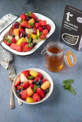 Fresh fruit salad in bowls, with a jar of quick and easy tea infused simple syrup and a box of We Are Tea's loose leaf White Peony tea.