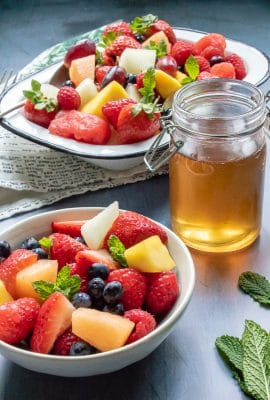 Two bowls full of fresh fruit salad and sprigs of mint, next to a jar of quick and easy tea simple syrup (sugar syrup infused with tea leaves)