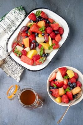 Big bowls of fruit salad with berries, melon, grapes and sprigs of mint, with a tea simple syrup in a jar for drizzling.
