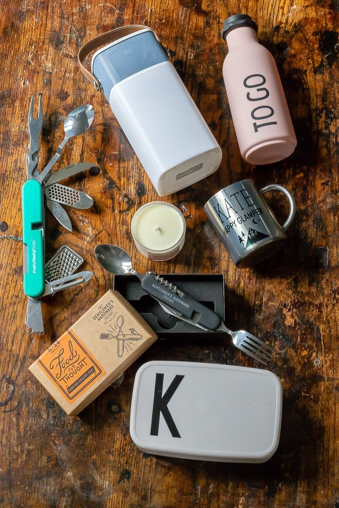 A bottle and camping items on a table.