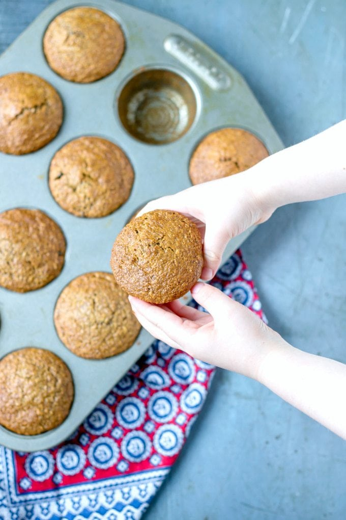 A child's hand holding a healthy bran muffin over a tray of muffins cooling