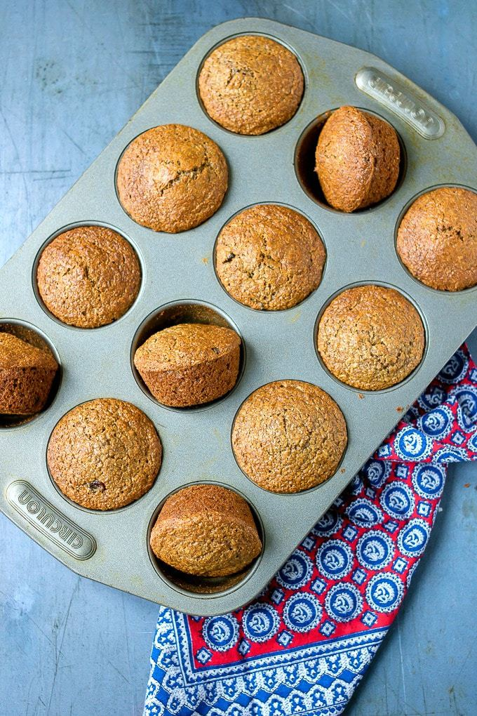 A tray of healthy bran muffins with some turned ready to take out of the pan