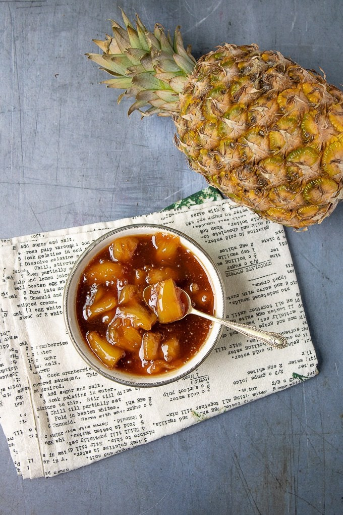 A bowl of quick and easy vanilla pineapple compote next to a pineapple
