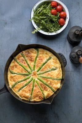 Overhead photo of sweet potato frittata with asparagus in a cast iron skillet, next to a salad