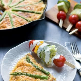 A slice of sweet potato frittata with asparagus on a plate with salad on a stick.