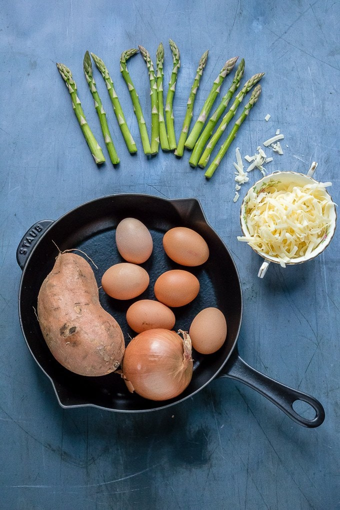 Ingredients for Sweet Potato Frittata with Asparagus - asparagus, cheese, eggs, onion, sweet potato, and a frying pan