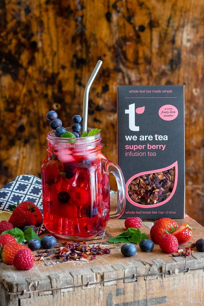A glass of berry iced tea with berries in the glass in front of a box of tea.
