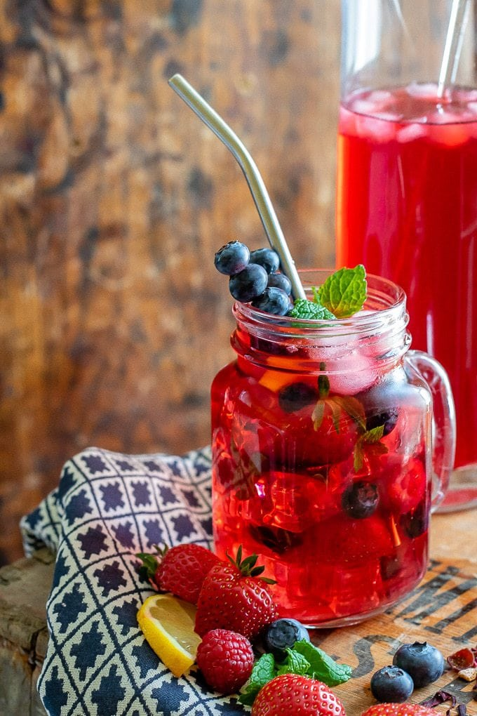 Close up of a glass of berry iced tea, with berries and mint in the glass with ice and a jug of berry iced tea in the background.
