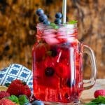 A glass of berry iced tea made with berry loose tea, ginger and berries. With berries on the table and sprigs of mint.
