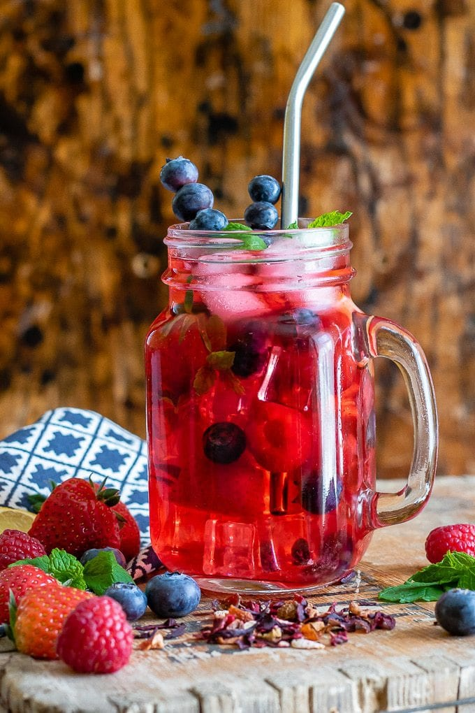 A glass of berry iced tea with berries on the table and sprigs of mint.