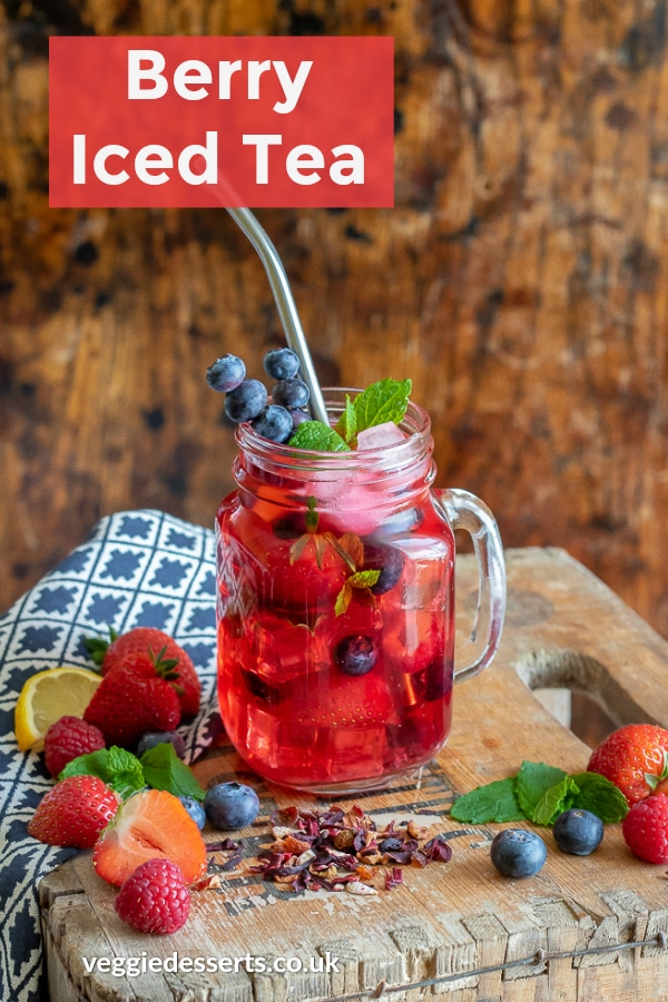Berry iced tea in a glass with fruit, with text overlay