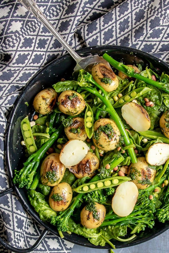 Close up of a blue patterned tea towel with a bowl of delicious vegan broccoli salad with potatoes, peas in pods and herbs