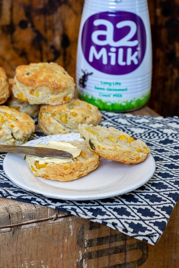 Corn and jalapeno scone with butter being spread onto it with a vintage knife in front of a bottle of A2 milk