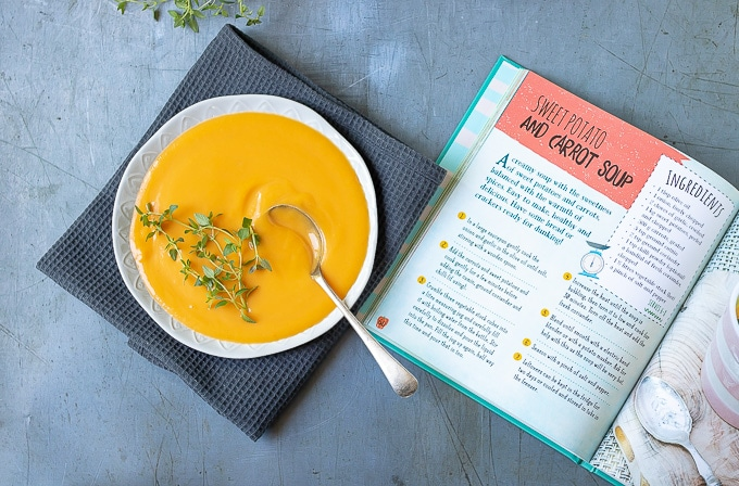 A bowl of carrot sweet potato soup next to the book Living on the Veg - a kids guide to vegetarianism,