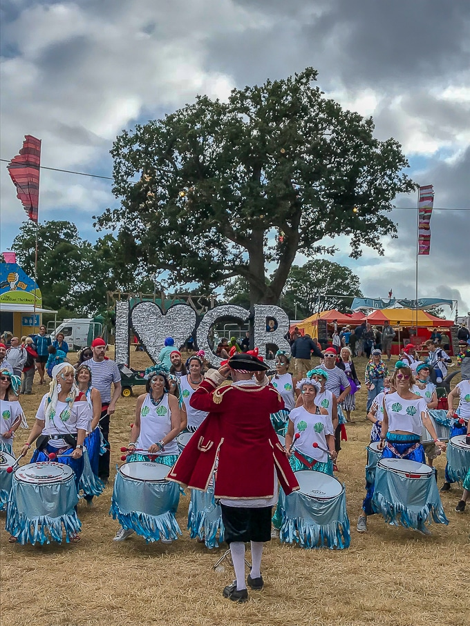 Battala drummers in front of the I heart CB sign at Camp Bestival 2018