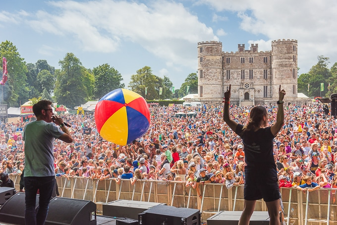 Dick and Dom throwing giant beach balls from the main stage with a view over the crowd to Lulworth Castle - Camp Bestival review 2018