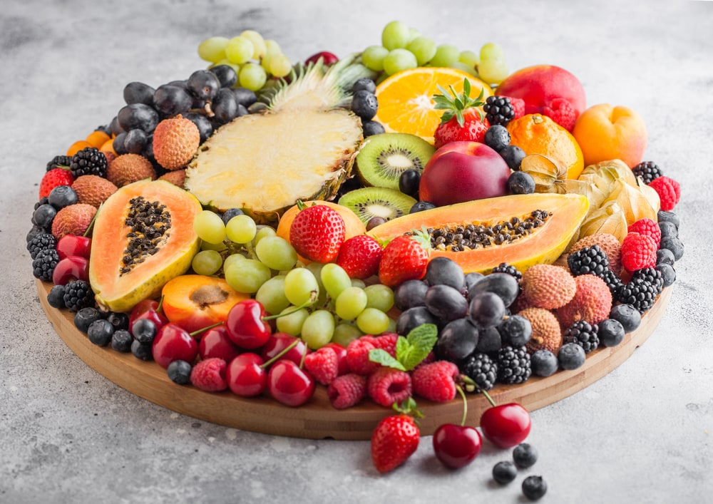 A fresh fruit tray with tropical fruit, berries, grapes and more.